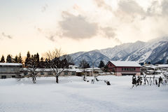 Snow covered alpine landscape at dusk. Alpine landscape of snow covered village and mountains at dusk (Honshu, Japan).  Villagers farm on the flat land at the Royalty Free Stock Photography