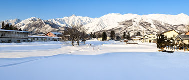 Snow covered alpine landscape of Japan during winter. Panoramic alpine landscape of snow covered village and mountains on Honshu, Japan.  Villagers farm on the Stock Photography