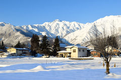 Snow covered alpine landscape of Japan during winter. Alpine landscape of snow covered village and mountains on Honshu, Japan.  Villagers farm on the flat land Royalty Free Stock Images