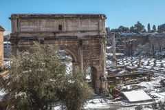 Snow Covered Trees of the Arch in the Roman Forum. Snow-covered and ancient Roman Forum left abandoned and closed on a snow day in Rome Stock Photo