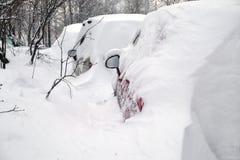 Snow-covered auto's in de straat van de stad in de winter worden opgesteld die Stock Foto
