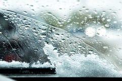 Snow-covered autowindscherm met gesmolten sneeuwdalingen en ruitewissers Vage lichten van het overgaan van auto's op de achtergro stock afbeelding