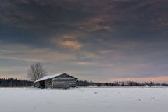Snow Covered Barn House Under Dramatic Skies Stock Photo