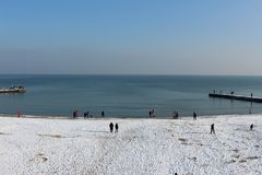 Snow-covered beach, sunny day. Sea in the city, walking to the beach stock photography