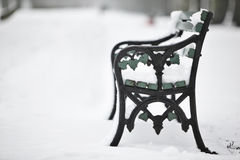 Snow covered bench. A snow covered bench in the park on a cold winter day Stock Images