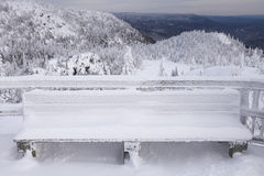 Snow covered bench. Picture of a wooden bench covered with snow. The bench is located at a lookout on top of a mountain Royalty Free Stock Photo