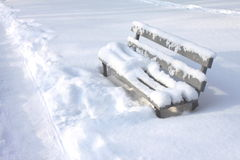 Snow-covered bench in city park between snow drifts Royalty Free Stock Images