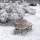 Snow-covered bench in city park at winter day Royalty Free Stock Photo