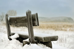Snow covered bench on coast. Closeup of snow covered wooden bench on coastline Royalty Free Stock Photography