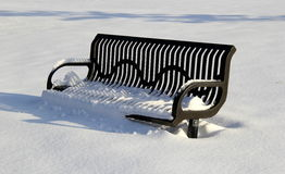 Snow covered bench in empty park Stock Photos