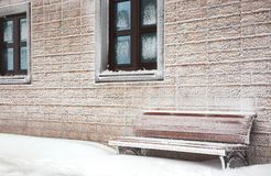 Snow-covered bench at  hoarfrost wall of house Stock Images