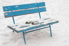 On a snow-covered bench lie forgotten childrens mittens Stock Photos