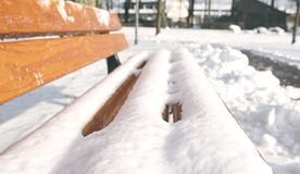 Snow-covered. Snow covered bench in a park Royalty Free Stock Photography