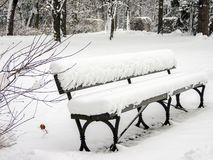 Snow-covered bench in the park stock photography