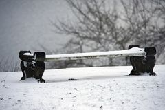 Snow-covered winter bench in a park Royalty Free Stock Photos