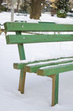 Snow covered bench in a park Stock Images