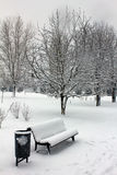 Snow covered bench in the park Stock Photo