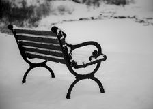 A snow covered bench peacefully resting in the park stock photo