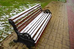Snow covered bench for relaxing in the park on the observation deck. Autumn, the first snow