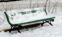 Snow-covered bench in winter park day Royalty Free Stock Image