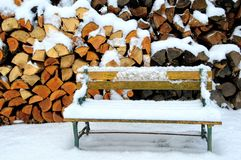 Snow Covered Bench by Woodpile. A snow covered child`s bench in front of a woodpile covered in snow royalty free stock image