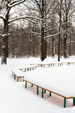 Snow-covered benches in meadow of city park Stock Photo