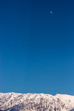 Snow-covered bergketen onder een hoge blauwe hemel en de maan Stock Fotografie
