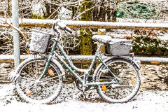 Snow covered bicycle leaning at a handrail Royalty Free Stock Images