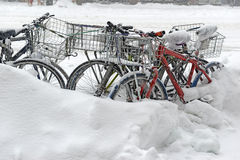 Snow covered bicycles on street after winter snowstorm Royalty Free Stock Image