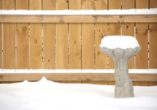 Snow covered birdbath in front of fence. A snow covered birdbath, made of sculptured cement, in front of a wooden fence. Focus is on the birdbath Royalty Free Stock Images