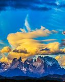 Snow-covered black rocks of Los Cuernos. Magnificent orange clouds in the rays of the sunset. The concept of extreme and active tourism. Torres del Paine stock images