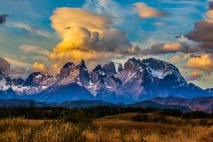 Snow-covered black rocks of Los Cuernos. Torres del Paine National Park. The concept of extreme and active tourism. Magnificent orange clouds in the sunset. Snow royalty free stock photography