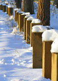 Snow covered bollards in the setting sun. Wooden bollards pop through a blanket of snow on the floor of South Lake Tahoe, Nevada. The remaining snow is melting Stock Photos