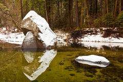 Snow Covered Boulders. Snowcapped boulders in the Merced River at Yosemite National Park, California Royalty Free Stock Images