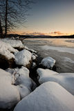 Snow covered boulders by the lake. Royalty Free Stock Photo