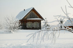 Snow covered branch in front of rustic wooden house at winter Stock Photo