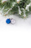Snow-covered branches of Christmas tree and only two shiny ball Royalty Free Stock Photo