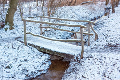 Snow covered bridge over small stream Royalty Free Stock Photo