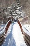 Snow covered bridge over stream Stock Photos