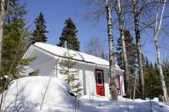 Snow covered cabin. Picture perfect: beautiful sunny day out at the small cabin with red door deep in the woods Royalty Free Stock Image