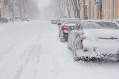 A snow covered car drives in winter storm royalty free stock photos