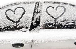 Snow-covered car. Hearts on a snow-covered car. Heart is a symbol of love. Valentine`s Day Royalty Free Stock Photo