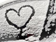 Snow-covered car. Hearts on a snow-covered car. Heart is a symbol of love. Valentine`s Day Royalty Free Stock Photography