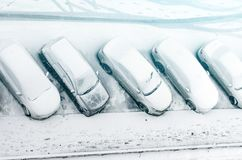 Snow-covered car in the parking lot. Urban scene. After a snowstorm. Clean automobile from the snow. Snow-covered car in the parking lot. Urban scene. After a Royalty Free Stock Image