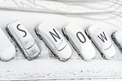 Snow-covered car in the parking lot. Urban scene. After a snowstorm. Clean automobile from the word snow. Snow-covered car in the parking lot. Urban scene Stock Photos