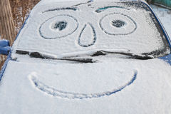 Snow-covered car with smiley Royalty Free Stock Photo
