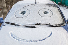 Snow-covered car with smiley Royalty Free Stock Photography