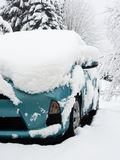 Snow covered car stuck in driveway. Passenger car in driveway covered by thick snow stock photo