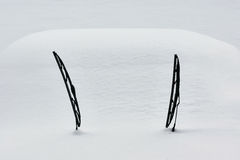Snow covered car. Two windscreen wipers poking out of a blanket of snow Stock Photo