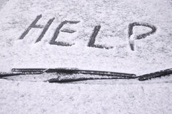 Snow covered car windscreen. With the word help written in the snow stock images